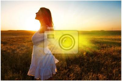 Bild Junge Frau auf Feld unter Sonnenunterganglicht