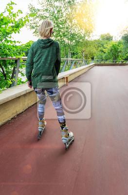 Bild Junge Frau auf Rollschuhen im Park