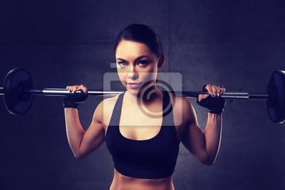 Junge Frau beugte Muskeln mit Hantel im Fitnessstudio