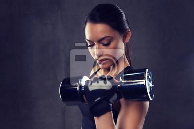 Junge Frau beugte Muskeln mit Hanteln im Fitnessstudio