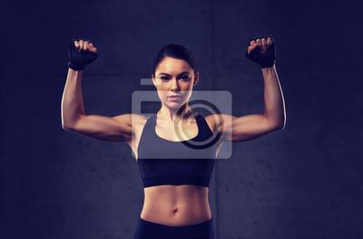 Junge Frau, die Muskeln im Fitnessstudio beugt