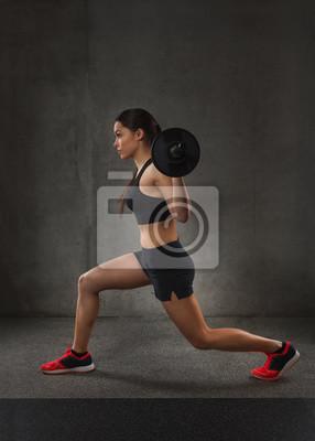 Junge Frau, die Muskeln mit barbell in der Turnhalle