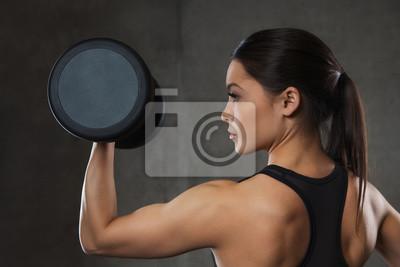 Junge Frau, die Muskeln mit Hanteln in der Turnhalle