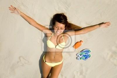 junge Frau im Bikini sonnt sich am Strand