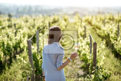 Bild Junge Frau mit Weinglas stand auf dem schönen Weinberg während des Sonnenuntergangs