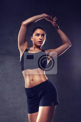 Junge Frau posiert und zeigt Muskeln in der Turnhalle