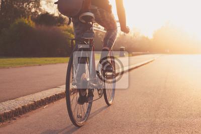 Bild Junge Frau Radfahren im Park bei Sonnenuntergang