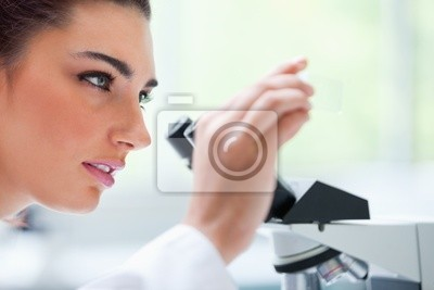 Junge Frau schaut auf einen Objektträger