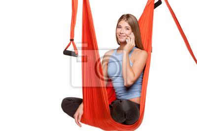 Junge Frau sitzt in der Hängematte für Anti-Schwerkraft-Antenne Yoga