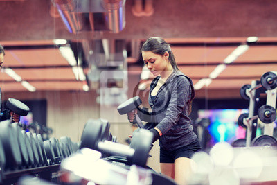 Junge Frau wählt Hanteln im Fitnessstudio