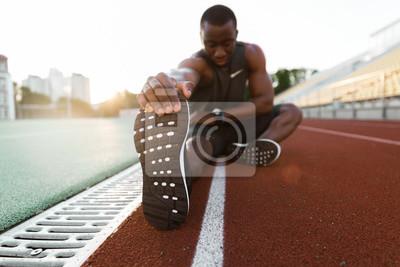 Bild Junge konzentrierte afrikanischen männlichen Athleten Stretching Beine