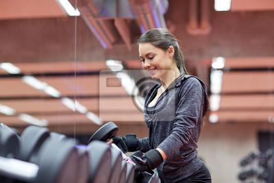 Junge lächelnde Frau wählen Hanteln in der Turnhalle