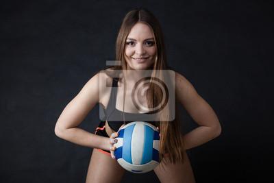 Junge Mädchen, die Volleyball auf schwarzem Hintergrund