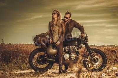 Bild Junge, stilvolle Caférennläuferpaare auf den Weinlesebrauchmotorrädern auf einem Gebiet.