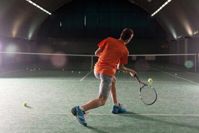 Bild Junge Tennisspieler treten die Bal