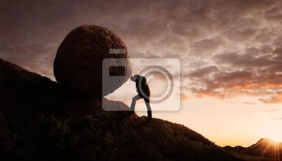 Bild Junger Geschäftsmann drückt großen Stein bergauf