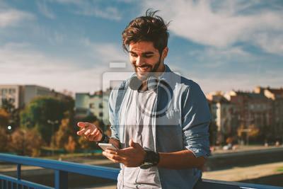 Bild Junger glücklicher Mann, der einen Smartphone in der Stadt verwendet