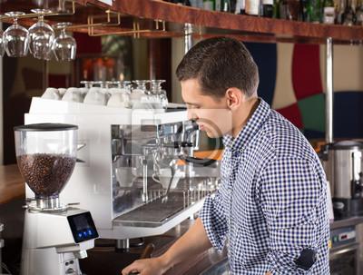 Bild Junger hübscher Barista, der Kaffee unter Verwendung der Kaffeemaschine des Handelsgrades herstellt.