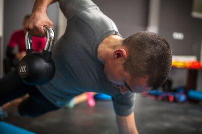 Bild Junger Mann Aufhebung Hantel und Kettlebell im Fitness-Center