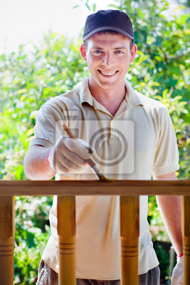 Junger Mann Malerei Holzzaun im Garten