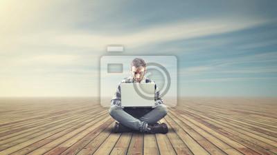 Junger Mann sitzt auf einem Holzboden