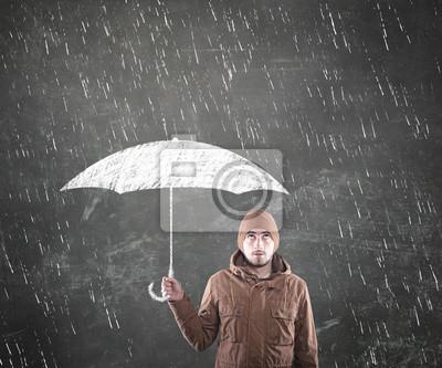 Junger Mann unter einem Regenschirm