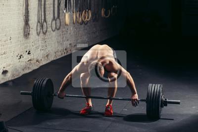 Bild Junger sportlicher Mann mit nacktem Oberkörper, der sich auf Gewichtheben trainiert. Kreuzschlitzausrüstung. Sport, Fitness - gesundes Lifestyle Konzept.