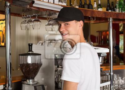 Bild Junges hübsches lächelndes barista im weißen Hemd- und Baseballhut, der nahe bei dem Handelsgradkaffeemacher steht.
