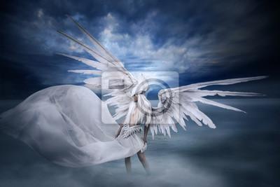 Junges Mädchen mit großen weißen Flügeln, stehend in den See in der Landschaft mit dramatischen Himmel und Nebel.