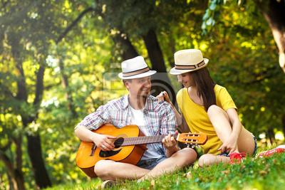 Bild Junges Paar in der Liebe spielt akustische Gitarre im Park