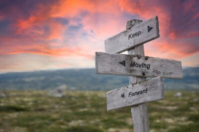 Bild keep moving forward text engraved in wooden signpost outdoors in nature during sunset and pink skies.