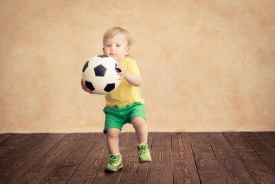 Kind gibt vor, ein Fußballspieler zu sein
