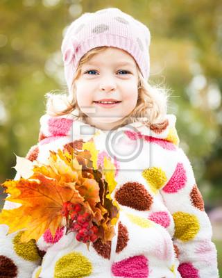Kind mit Haufen von Ahorn-Blätter