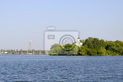 Kirche in den Bäumen am Ufer des Flusses