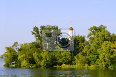 Kirche in den Bäumen am Ufer des Flusses, blauer Himmel und Reflexion im Wasser