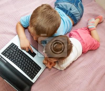 Kleine Mädchen und Jungen vor Laptop liegend