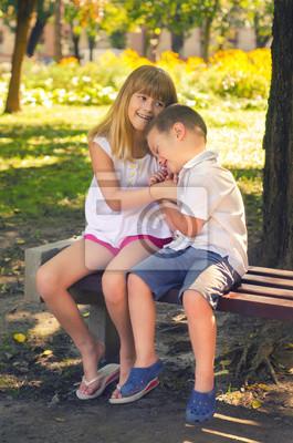 Kleiner Junge und kleines Mädchen spielen im Park auf der Bank am sonnigen Sommertag
