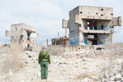 Bild kleines Kind in Jacke steht gegen Ruinen des Gebäudes als Folge eines Kriegskonflikts