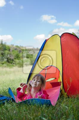 Kleines Mädchen, das auf der Matte in der Nähe bunten Zelt