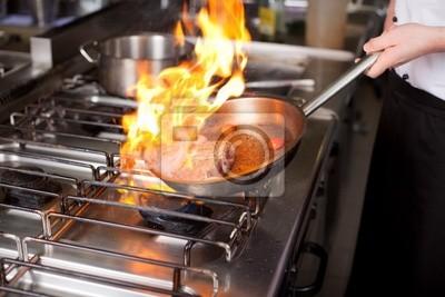 koch flambiert fleisch in der pfanne