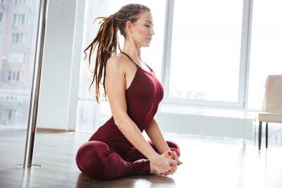 Bild Konzentrierte hübsche Frau macht Yoga im Studio