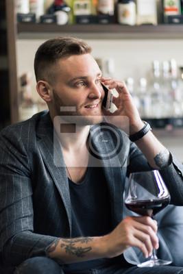 Bild Konzept Foto von reichen Menschen Luxus Leben. Erwachsene erfolgreiche elegante Geschäftsmann Tragen Anzug und trinken Wein auf der Dachterrasse in Luxus-Penthouse