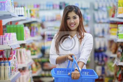 Lächelnd asiatische Mädchen hält Korb im Supermarkt