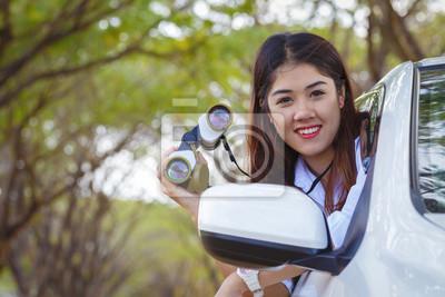 Lächelnd asiatische Mädchen mit Fernglas auf dem Auto
