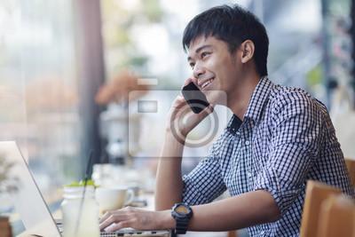 Lächelnd asiatischen Geschäftsmann macht einen Anruf während der Entspannung mit Notebo
