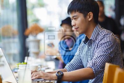 Lächelnd asiatischen Geschäftsmann mit Laptop im Café