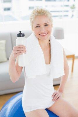 Lächelnde Frau mit der Wasserflasche, die auf Übungsball sitzt