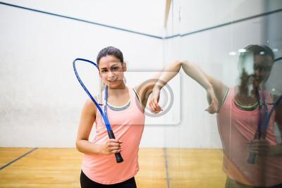 Lächelnde Frau mit einem Squash-Schläger