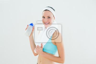 Lächelnde Frau mit Tuch um den Hals, der Wasserflasche hält