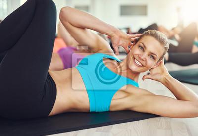 Lächelnde Frau tun Bauch Übungen auf Matte in der Turnhalle